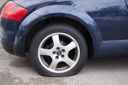 A picture of a car with a flat tire that needs repairing in York.